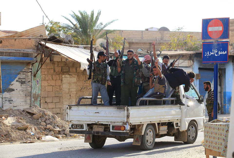 Photo -   Syrian rebels ride on the back of a truck in Tel Abyad, Syria, Friday, Oct. 5, 2012. On Friday, a Syrian mortar round hit inside Turkey, causing no injuries, and Turkish troops returned fire, the state-run news agency Anadolu said late Friday, and Turkey deployed more troops near to the border with Syria. (AP Photo)