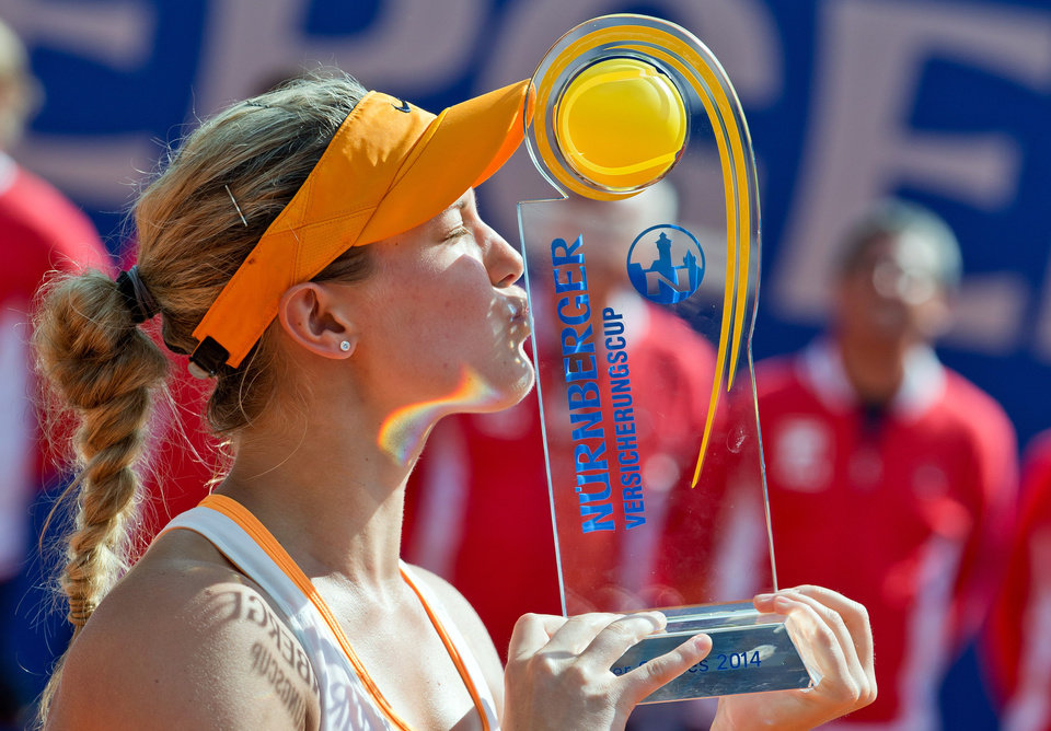 Photo - Canadian Eugenie Bouchard kisses the trophy after defeating Czech  Karolina Pliskova at the WTA final in Nuremberg, Germany, Saturday, May 24, 2014. Bouchard won 6-2, 4-6, 6-3. (AP Photo/dpa, Daniel Karmann)