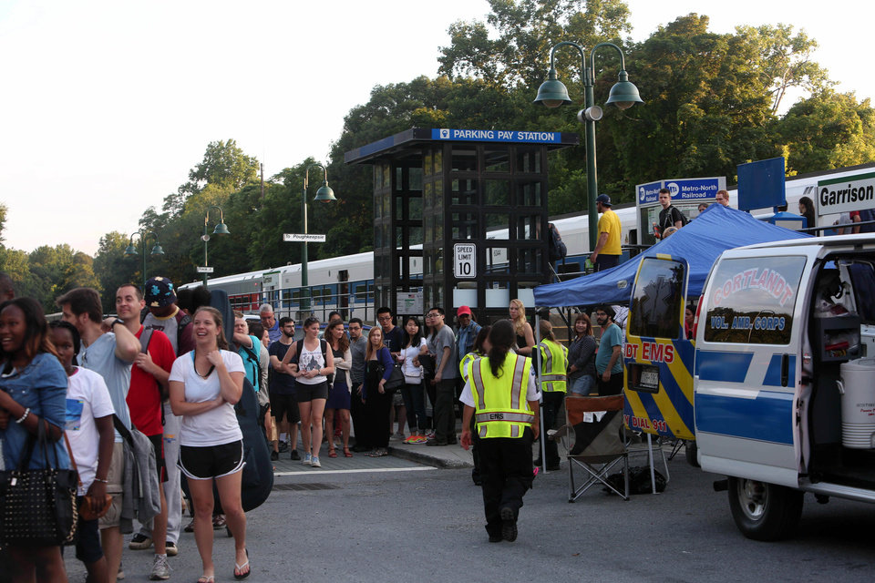Photo - Train passengers wait in lines to board buses at the Garrison train station after a rock slide on the railroad tracks between Peekskill and Garrison forced the closure of both north and southbound tracks Saturday, July 19, 2014, in Garrison, N.Y. Tumbling rocks north of New York City have damaged a stretch of train tracks in the nation's second-largest commuter rail system, suspending service and leaving hundreds of passengers without rides. (AP Photo/The Journal News, Frank Becerra Jr.) NYC OUT, NO SALES, ONLINE OUT, TV OUT, NEWSDAY INTERNET OUT; MAGS OUT