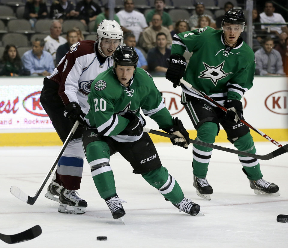 Dallas Stars center Cody Eakin (20) and Colorado Avalanche center Matt Duchene (9) compete for a loose puck as Stars defenseman Jamie Oleksiak (5) watches in the second period of a preseason NHL hockey game on Thursday, Sept. 26, 2013, in Dallas. (AP Photo/Tony Gutierrez)