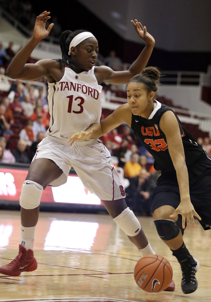 Photo - Oregon State's Deven Hunter, right, drives the ball against Stanford's Chiney Ogwumike (13) during the first half of an NCAA college basketball game Sunday, Jan. 5, 2014, in Stanford, Calif. (AP Photo/Ben Margot)