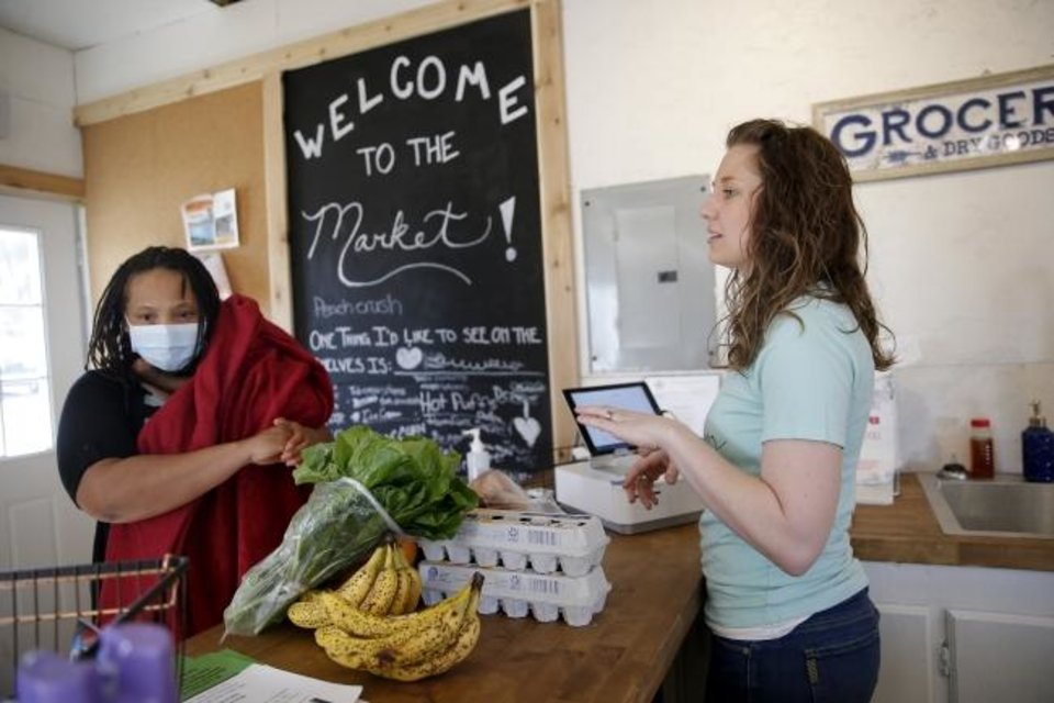 Photo -  Shaquice Muyanga places her groceries at the counter so Restore OKC executive director Caylee Dodson may check her out on Thursday at The Market at Restore OKC, 2222 NE 27. [Bryan Terry/The Oklahoman]