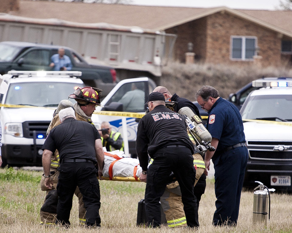 Photo - Emergency personnel carry the driver of a black Cadillac with Colorado plates who was involved in a high speed chase and shootout with police in Decatur, Texas, Thursday, March 21, 2013. The driver led police on a gunfire-filled chase through rural Montague County, crashed his car into a truck in Decatur, opened fire on authorities and was shot, officials said.  Texas authorities are checking whether the Cadillac is the same car spotted near the home of Colorado prisons chief Tom Clements, who was shot and killed when he answered the door Tuesday night. (AP Photo/Wise County Messenger, Jimmy Alford) MANDATORY CREDIT, MAGS OUT