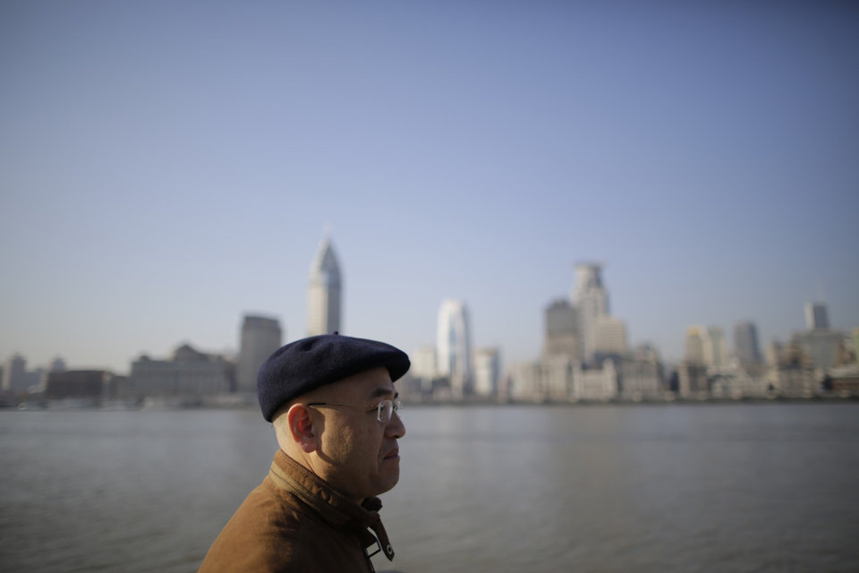 ADVANCE FOR USE MONDAY, MARCH 18, 2013 AND THEREAFTER - In this Jan. 28, 2013 photo, Chinese-born U.S. scientist Hu Zhicheng walks along the waterfront promenade of the Huangpu River in Shanghai, China. In Shanghai, he lives life as a free man, able to do anything except depart the country. Six thousand miles away in California, his family remains locked in their own emotional prisons: The wife who was left to raise two children alone. The son, just 13 when this started, who speaks bitterly of missing out on father-son moments. (AP Photo/Eugene Hoshiko)