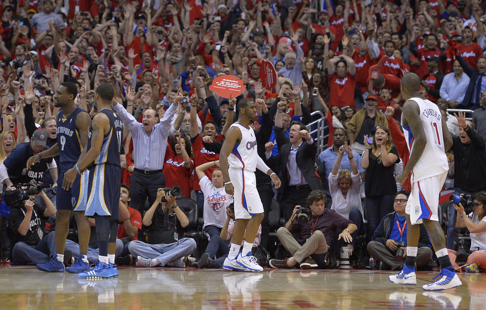 Photo - Fans celebrate after Los Angeles Clippers guard Chris Paul, center, hit a two-point shot with 0.1seconds left as guard Jamal Crawford, right, and Memphis Grizzlies guard Tony Allen, left, and guard Mike Conley look on during the second half of Game 2 of a first-round NBA basketball playoff series, Monday, April 22, 2013, in Los Angeles. The Clippers won 93-91. (AP Photo/Mark J. Terrill)