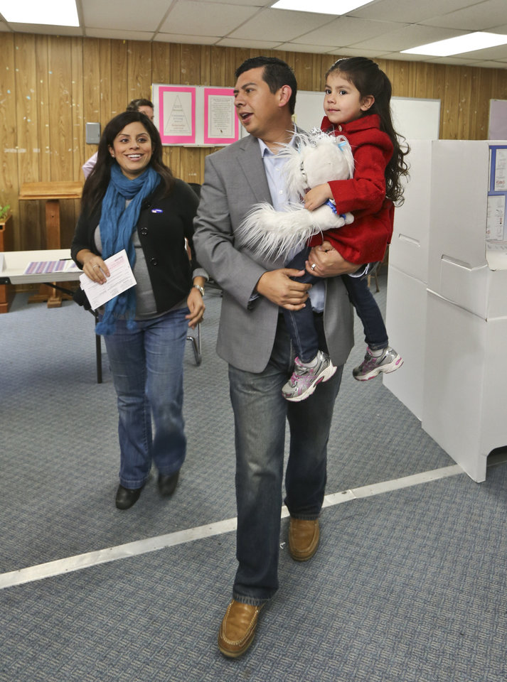 Photo - San Diego mayoral candidate David Alvarez, carries his daughter, Izel, as he and his wife, Xochitl, leave the polling location where they voted in the Logan Heights neighborhood where Alvarez grew up and still lives Tuesday, Feb. 11, 2014 in San Diego. (AP Photo/Lenny Ignelzi)
