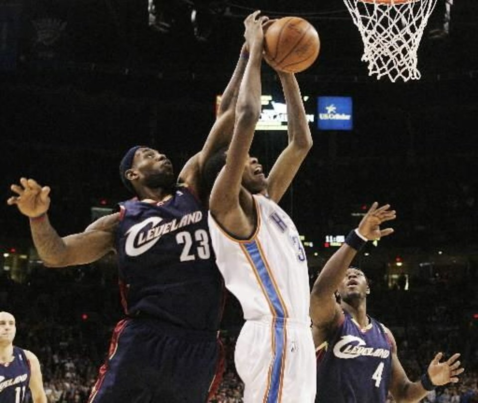 Photo - Oklahoma City  Thunder guard Kevin Durant, center, has the ball knocked away by Cleveland Cavaliers forward LeBron James, left, as he attempts to shoot between James and forward Ben Wallace, right, in the first quarter of an NBA basketball game in Oklahoma City, Sunday, Dec. 21, 2008. Durant had 26 points for the  Thunder, but Cleveland won 102-91. (AP Photo/Sue Ogrocki)