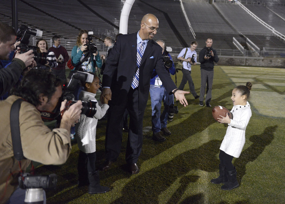 Photo - Penn State's new football coach James Franklin prepares to catch a football from his daughter, Addison, 5, after being introduced during an NCAA college football news conference at Beaver Stadium, Saturday, Jan. 11, 2014, in State College, Pa. Holding her father's hand is Shola, 6. (AP Photo/John Beale)