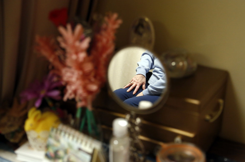 Photo -  Mabel Smith, whose hand is reflected in a mirror in her room, has lived at Fairview Fellowship Home & Village in Fairview for about six months. [Photo by Sarah Phipps, The Oklahoman]