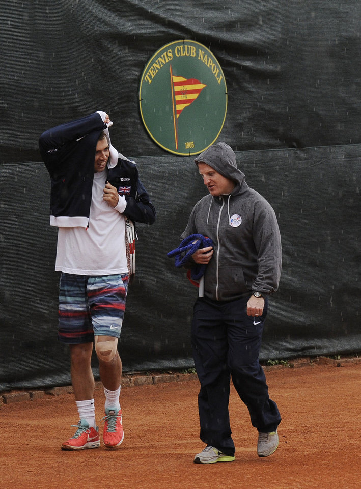 Photo - Britain's James Ward, left,  walks off the court as rain delays the Davis Cup World Group quarterfinal match against Italy's Fabio Fognini in Naples, Italy, Friday April 4, 2014. (AP Photo/Salvatore Laporta)