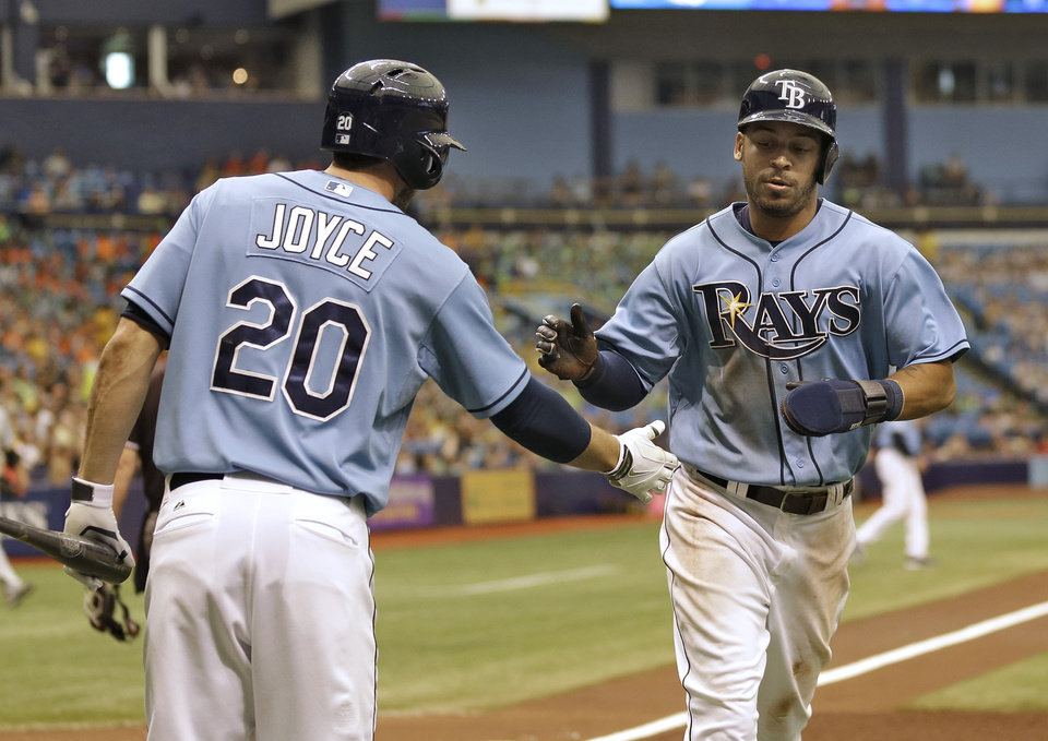 Photo - Tampa Bay Rays' Desmond Jennings, right, shakes hands with on-deck batter Matt Joyce after scoring on a triple by teammate Ben Zobrist off Pittsburgh Pirates starting pitcher Charlie Morton during the first inning of an interleague baseball game Wednesday, June 25, 2014, in St. Petersburg, Fla. (AP Photo/Chris O'Meara)