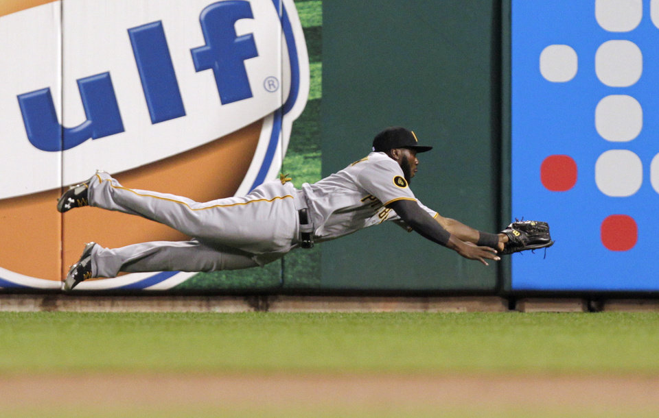 Photo - Pittsburgh Pirates right fielder Josh Harrison makes a diving catch on a ball hit by St. Louis Cardinals' Jhonny Peralta in the second inning of a baseball game, Monday, July 7, 2014 in St. Louis. (AP Photo/Tom Gannam)