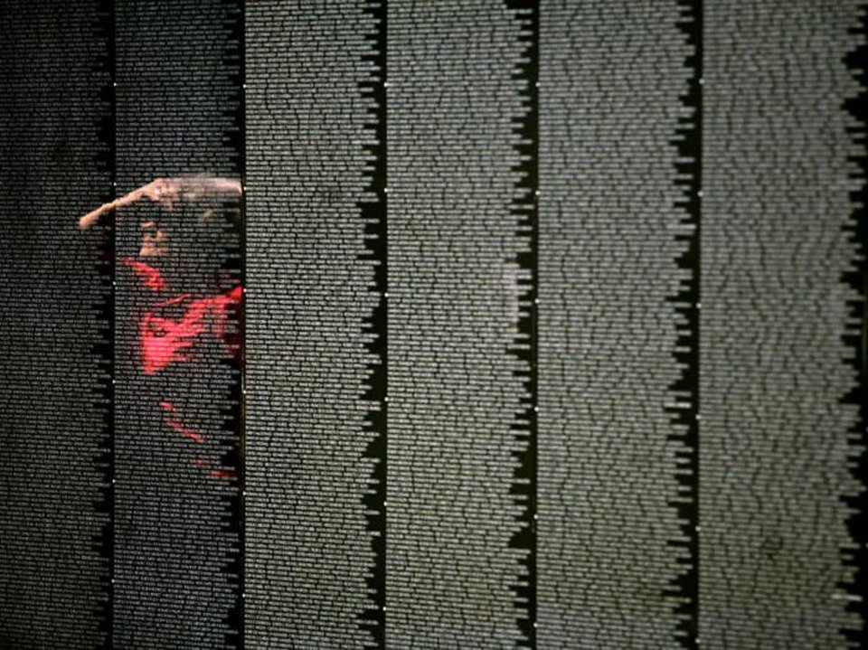 Photo -  Mary Morse, of Shawnee, is reflected in The Moving Wall exhibit, as she look at the memorial, a replica of Vietnam Veterans Memorial in Washington DC, at  Woodland Park in Shawnee , Okla., on Sunday, August 23, 2009. By John Clanton, The Oklahoman ORG XMIT: KOD