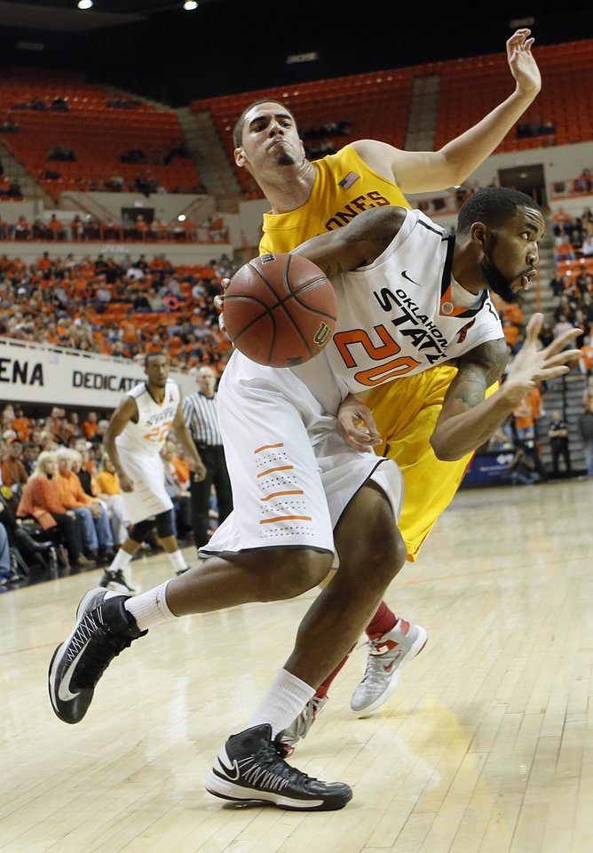 Photo - Oklahoma State Cowboys' Michael Cobbins (20) drives past Iowa State Cyclones' Georges Niang (31) during the college basketball game between the Oklahoma State University Cowboys (OSU) and the Iowa State University Cyclones (ISU) at Gallagher-Iba Arena on Wednesday, Jan. 30, 2013, in Stillwater, Okla.  Photo by Chris Landsberger, The Oklahoman