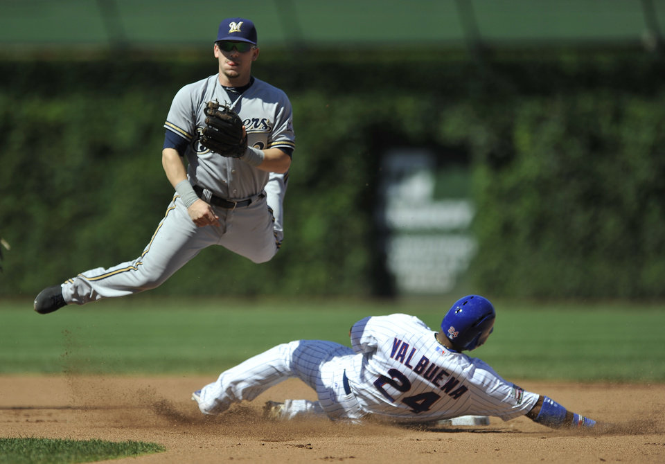 Photo - Milwaukee Brewers second baseman Scooter Gennett watches his throw to first base after forcing out Chicago Cubs' Luis Valbuena at second base during the second inning of a baseball game in Chicago, Monday, Sept. 1, 2014. (AP Photo/Paul Beaty)