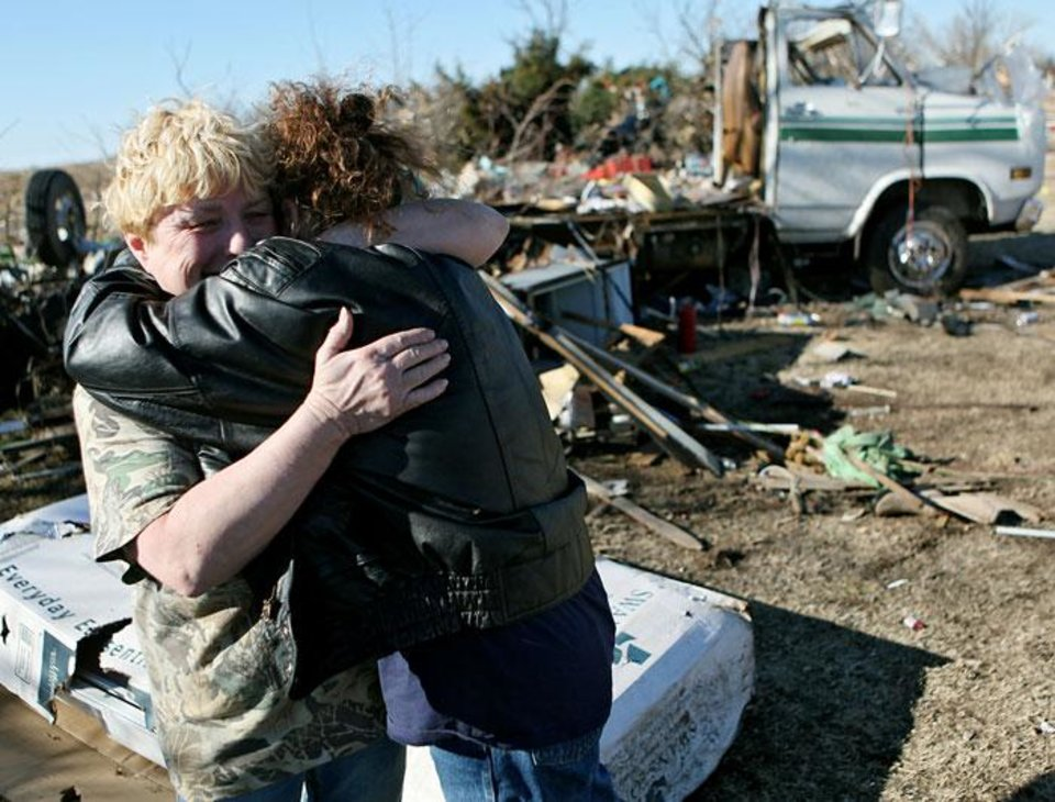 Photo -  Margie Hughes (left) gets a hug from her sister Neda Wilson as they look at Margie's destroyed home following deadly storms around Lone Grove, Okla., Feb. 11, 2009. By John Clanton, The Oklahoman