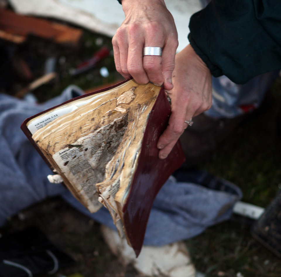 Donna Sebastian found her Bible in the debris of her home on Carlisle Road Friday, March 2, 2012 in Boone County, Ky. Powerful storms stretching from the Gulf Coast to the Great Lakes flattened buildings in several states, wrecked two Indiana towns and bred anxiety across a wide swath of the country in the second powerful tornado outbreak this week.  (AP Photo/The Cincinnati Enquirer, Patrick Reddy) MANDATORY CREDIT;  NO SALES   ORG XMIT: OHCIN105