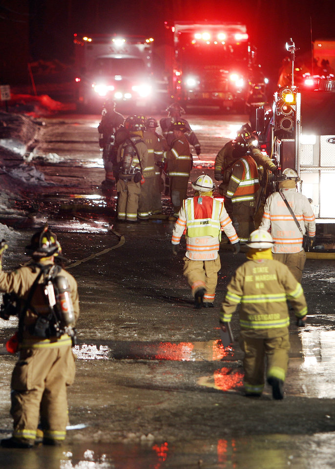Photo - Emergency crews from several towns work an area outside the New Hampshire Ball Bearing plant after an explosion, Monday, Feb. 10, 2014 in Peterborough, N.H. At least 13 people were injured, but a company spokeswoman says none of the injuries appears to be life-threatening. (AP Photo/Jim Cole)