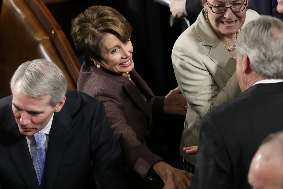 Photo - House Minority Leader Nancy Pelosi of Calif., center, and Sen. Rob Portman, R-Ohio, arrive for President Barack Obama's State of the Union address on Capitol Hill in Washington, Tuesday Jan. 28, 2014. (AP Photo/J. Scott Applewhite)