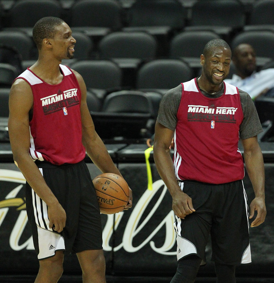 Photo - Miami Heat forward Chris Bosh, left with teammate guard Dwyane Wade laughduring NBA basketball practice, Saturday, June 15, 2013, in San Antonio. The Heat take on the San Antonio Spurs in Game 5 of the NBA Finals on Sunday, with the best-of-seven games series even at 2-2.(AP Photo/El Nuevo Herald, David Santiago)  MAGS OUT