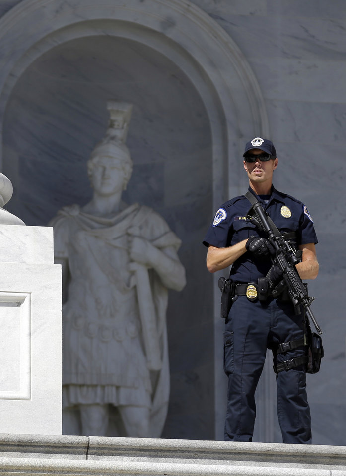 A Capitol Hill Police officer stands with a rifle at the ready, on Capitol Hill in Washington, Tuesday, Sept. 11, 2012, before a Congressional remembrance ceremony for the events of 9/11. (AP Photo/Alex Brandon) ORG XMIT: DCAB110