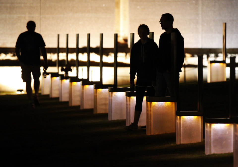 Photo - People are silhouetted as they walk through the Field of Empty Chairs at the Oklahoma City National Memorial before the Oklahoma City Memorial Marathon in Oklahoma City, Sunday, April 24, 2016. Photo by Nate Billings, The Oklahoman