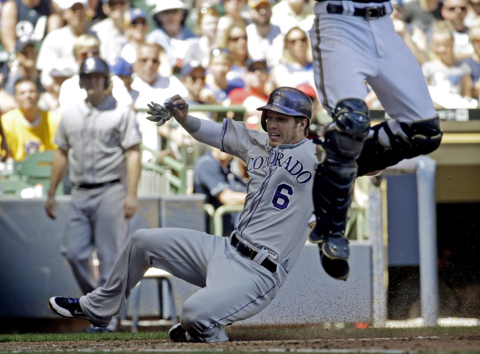 Photo - Colorado Rockies' Corey Dickerson (6) scores as Milwaukee Brewers catcher Jonathan Lucroy leaps for a throw during the fifth inning of a baseball game Sunday, June 29, 2014, in Milwaukee. (AP Photo/Morry Gash)