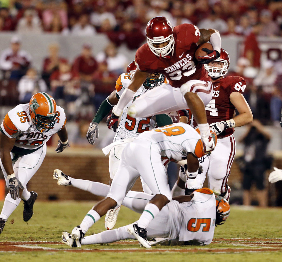 Photo - Trey Millard (33) leaps over defenders during the second half of the college football game between the University of Oklahoma Sooners (OU) and Florida A&M Rattlers at Gaylord Family-Oklahoma Memorial Stadium in Norman, Okla., Saturday, Sept. 8, 2012. Photo by Steve Sisney, The Oklahoman