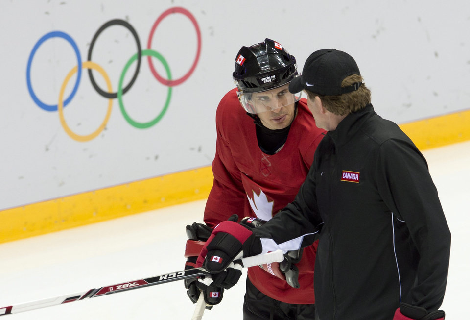 Photo - Team Canada's head coach Mike Babcock, right,  speaks with Sidney Crosby during practice at the Sochi Winter Olympics Tuesday Feb. 11, 2014, in Sochi, Russia. (AP Photo/The Canadian Press, Adrian Wyld)