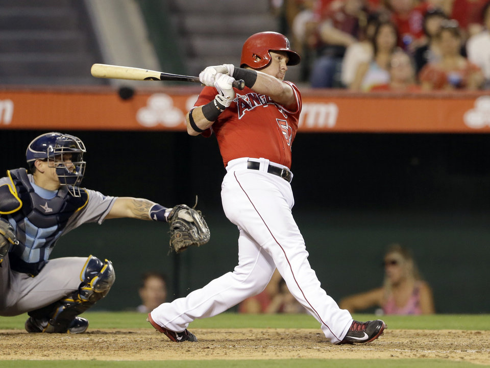 Photo - Los Angeles Angels' Kole Calhoun singles in a run against the Tampa Bay Rays catcher Jose Lobaton at left, in the third inning of a baseball game in Anaheim, Calif., Monday, Sept. 2, 2013. (AP Photo/Reed Saxon)