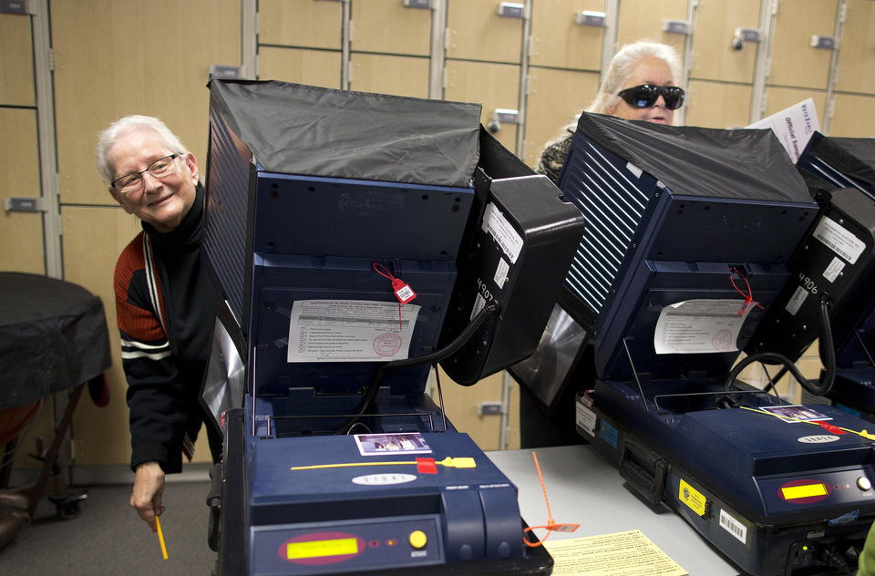 Photo -   A woman who identified herself as Dolores, left, looks for an election worker to help her with her voting machine while casting her ballot on Election Day, Tuesday, Nov. 6, 2012, in Las Vegas. (AP Photo/Julie Jacobson)