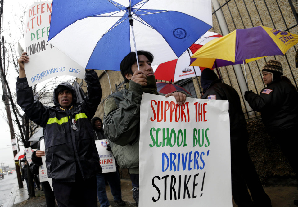 Photo - Bus drivers and supporters walk a picket line in front of a bus depot in New York, Wednesday, Jan. 16, 2013.  More than 8,000 New York City school bus drivers and matrons went on strike over job protection Wednesday morning, leaving some 152,000 students, many disabled, trying to find other ways to get to school.  (AP Photo/Seth Wenig)