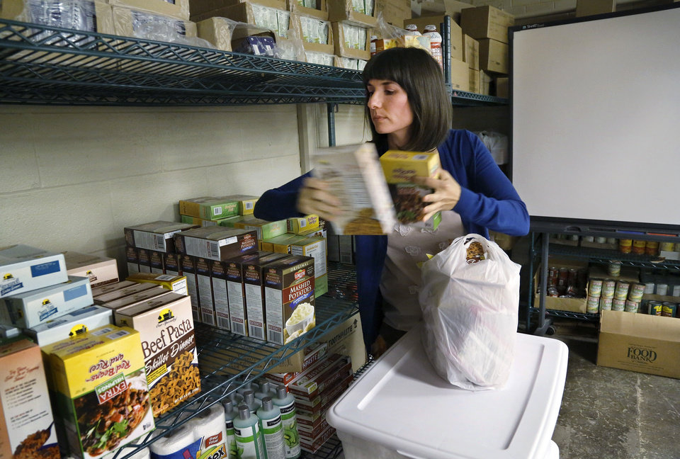 Amber Dubuc, seventh-grade counselor at Taft Middle School, grabs food from shelves in the school\'s