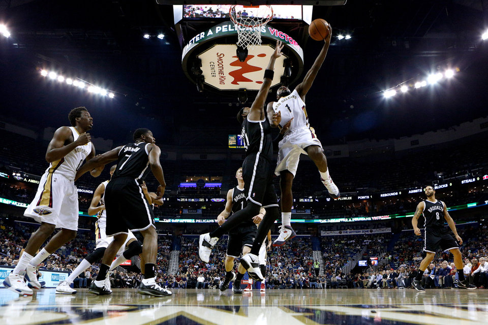 Photo - New Orleans Pelicans forward Tyreke Evans (1) drives against Brooklyn Nets forward Paul Pierce, center, during the first half of an NBA basketball game in New Orleans, Monday, March 24, 2014. (AP Photo/Jonathan Bachman)