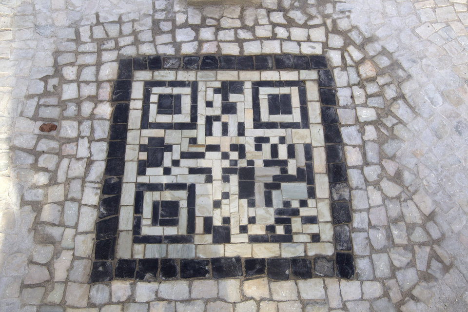 A two-dimensional bar code, or QR code, as they\'re known, made from black and white stones covers a sidewalk near the beach in Rio de Janeiro, Brazil, Friday, Jan. 25, 2013. The QR codes are being placed at tourist spots which can be scanned with a mobile device for information about the site. (AP Photo/Silvia Izquierdo)