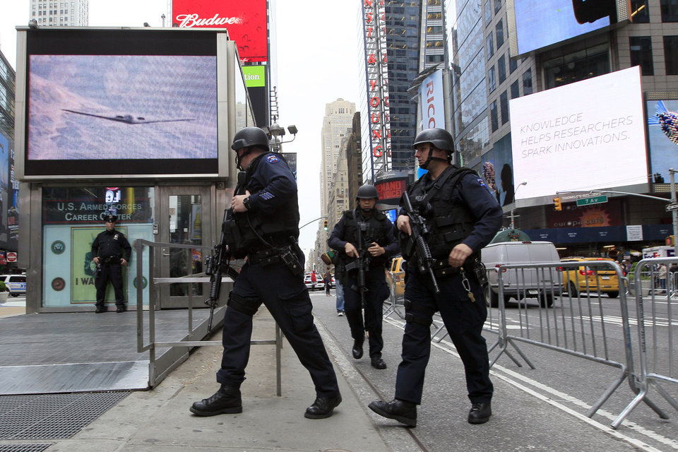 Photo - New York City police officers with Operation Hercules arrive at the Armed Forces recruitment center in New York's Times Square on Monday, May 2, 2011. President Barack Obama announced Sunday night that Osama bin Laden was killed in Pakistan in an operation led by the United States. (AP Photo/Mary Altaffer) ORG XMIT: NYMA108