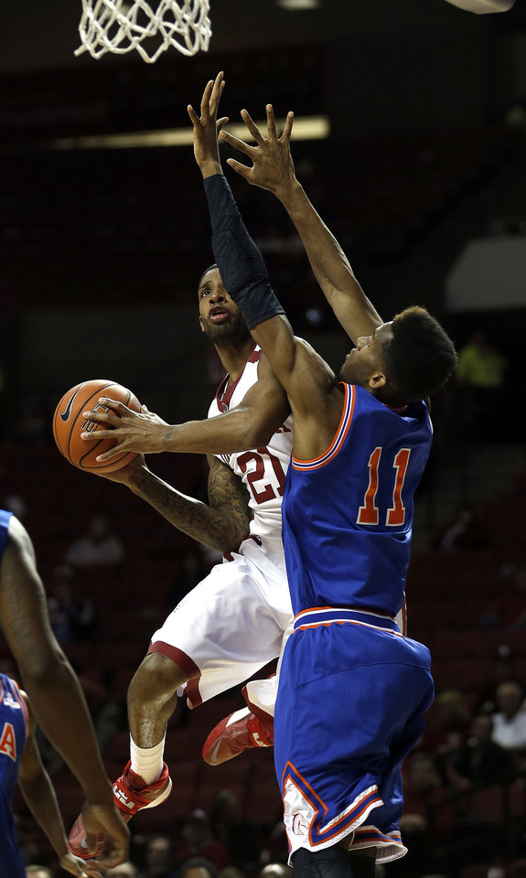 Oklahoma's Cameron Clark (21) shoot a lay up as Texas-Arlington's Brandon Williams (11) during the men's college basketball game between the University of Oklahoma and UT-Arlington, at the LLoyd Noble Center in Norman, Okla. Tuesday, Dec. 17, 2013. Photo by Sarah Phipps, The Oklahoman