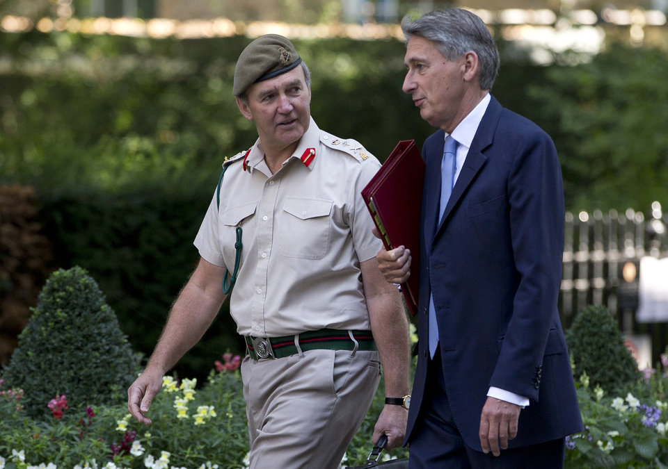 Photo - Britain's Defence Secretary Philip Hammond, right, and the Chief of Defense Staff Gen. Nick Houghton arrive for a national security meeting on the situation in Syria at Downing Street in London, Wednesday, Aug. 28, 2013. Britain says it will put forward a resolution Wednesday to the U.N. Security Council condemning the Syrian government for the alleged chemical attack that has killed hundreds of civilians. A statement from Prime Minister David Cameron's office said Britain would seek a measure