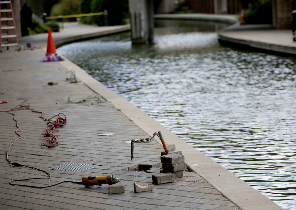 Photo -  A light post lays on the sidewalk Tuesday as work is done to repair them after two men were shocked Sunday night after one fell into the Bricktown canal.  [Photo by Sarah Phipps, The Oklahoman]
