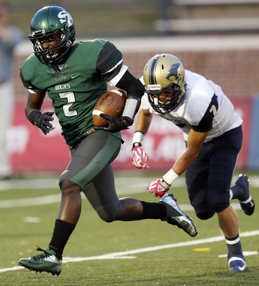 Photo - Edmond Santa Fe's Trevan Smith gets by Southmoore's Tyler Painter on his way to a touchdown during a high school football game between Edmond Santa Fe and Southmoore at Wantland Stadium in Edmond, Okla., Thursday, Sept. 20, 2012. Photo by Nate Billings, The Oklahoman