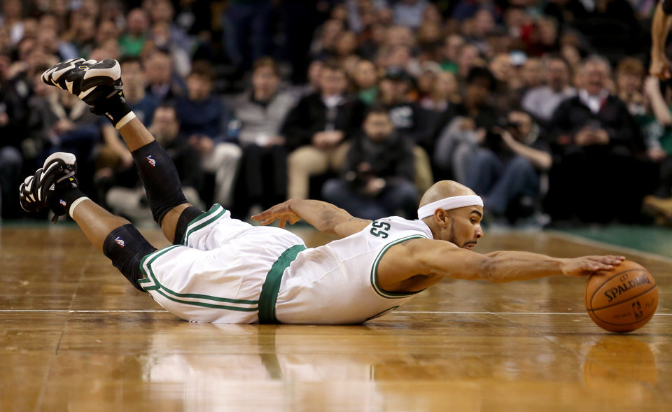 Photo - Boston Celtics point guard Jerryd Bayless dives for a loose ball during the first half of an NBA basketball game against the Sacramento Kings, Friday, Feb. 7, 2014, in Boston. (AP Photo/Mary Schwalm)