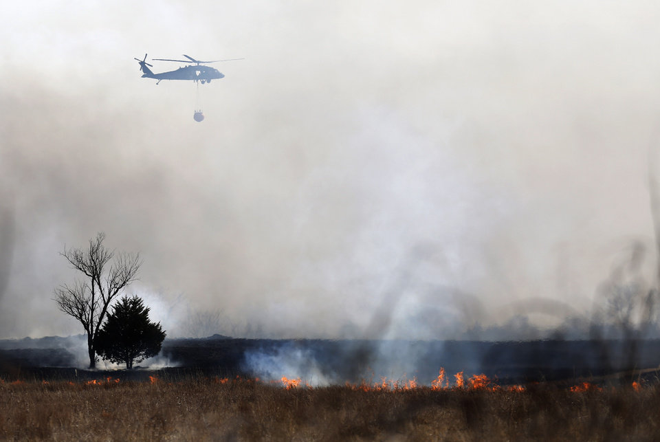 Photo -  An Army National Guard helicopter bring water to a wildfire Sunday in southeast Oklahoma City. [Photo by Sarah Phipps, The Oklahoman]