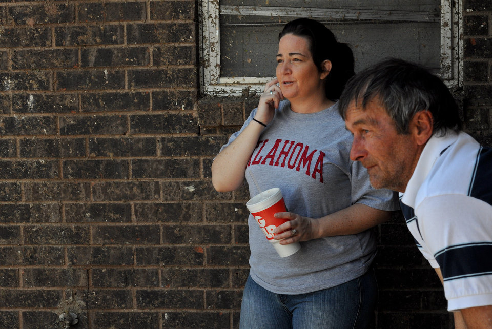 Photo - Summer Roberts and her father-in-law Freddy Roberts look out over the ruined lawn of her family's home in Moore, Okla. on May 22, 2013. Photo by KT King, The Oklahoman
