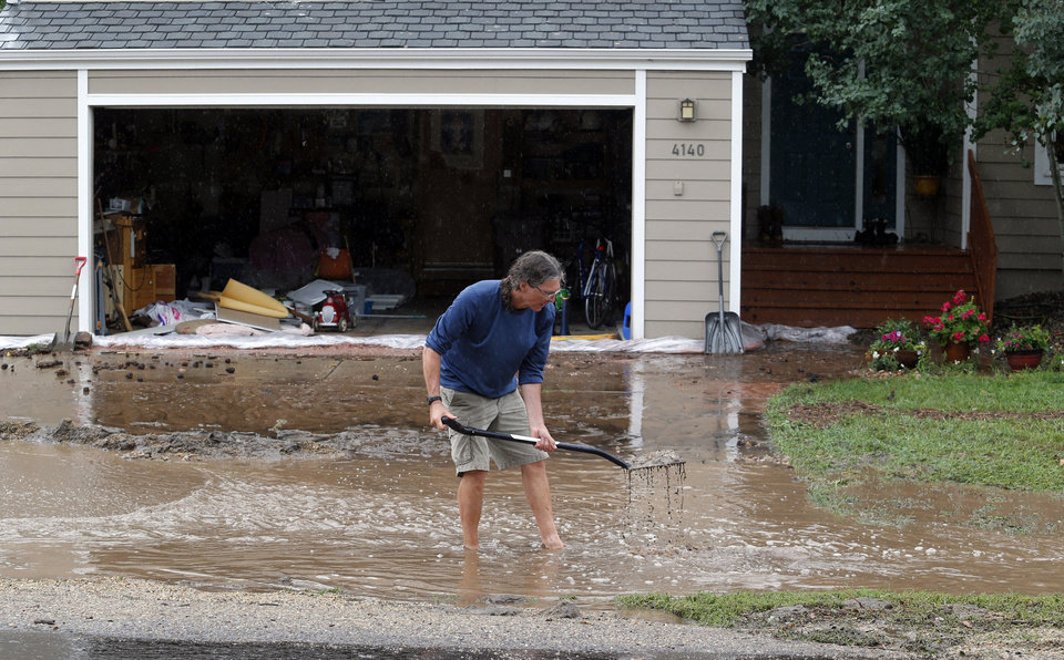 Photo - Brian Flynn, of Oregon, clears a drain in front of his sister's home in Boulder, Colo., on Thursday, Sept. 12, 2013. Flash flooding in Colorado has cut off access to towns, closed the University of Colorado in Boulder and left at least three people dead.(AP Photo/Ed Andrieski)
