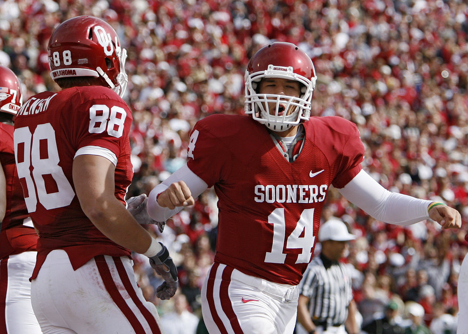 Photo - Sam Bradford (14) reacts with Eric Mensik (88) after the Sooners first touchdown during the first half of the college football game between the University of Oklahoma Sooners (OU) and the Baylor University Bears at Gaylord Family-Oklahoma Memorial Stadium on Saturday, Oct. 10, 2009, in Norman, Okla. 
