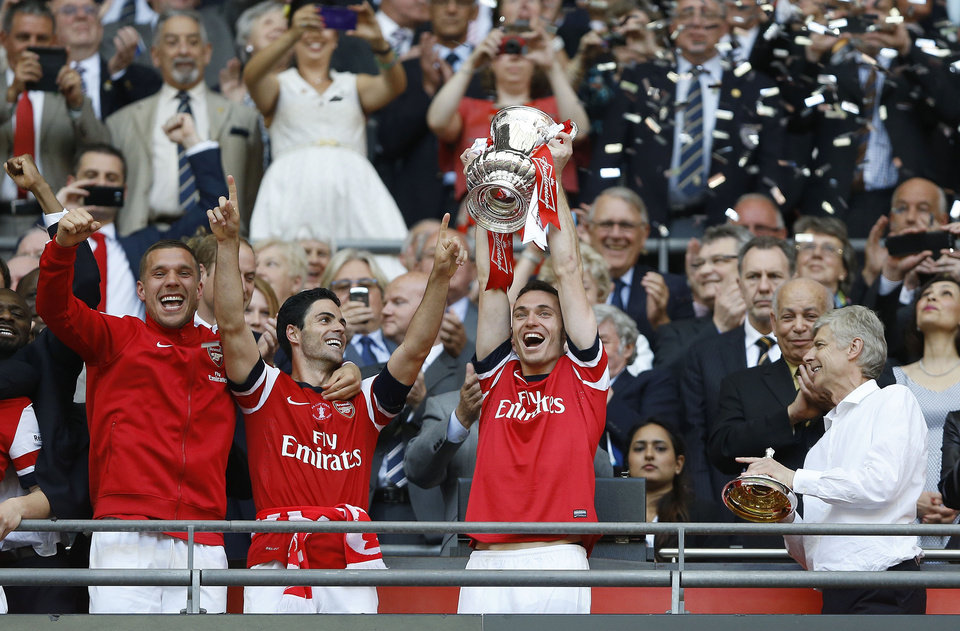 Photo - Arsenal's club captain Thomas Vermaelen holds the trophy aloft as he celebrates after his team won the English FA Cup final soccer match between Arsenal and Hull City at Wembley Stadium in London, Saturday, May 17, 2014. Arsenal won 3-2 after extra-time. (AP Photo/Kirsty Wigglesworth)