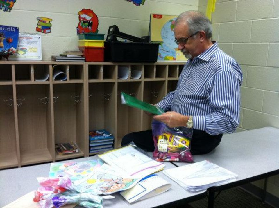 Fourth grade teacher John Roberts looks through Jasmen Gonzalez's schoolwork Tuesday afternoon at John Glenn Elementary School in Oklahoma City. Jasmen, 10, was fatally stabbed in Texas over the weekend. <strong>TIFFANY GIBSON</strong>
