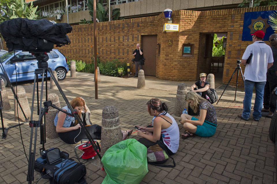 Photo - Journalists camp outside the police station in Brooklyn, east of Pretoria, Monday, Feb. 18, 2013 where athlete, Oscar Pistorius spent a fifth day in custody charged with the shooting death of his girlfriend Reeva Steenkamp. Pistorius faces a bail hearing in court tomorrow on the same day that Steenkamp is to be cremated in her home town Port Elizabeth on the east coast. (AP Photo)