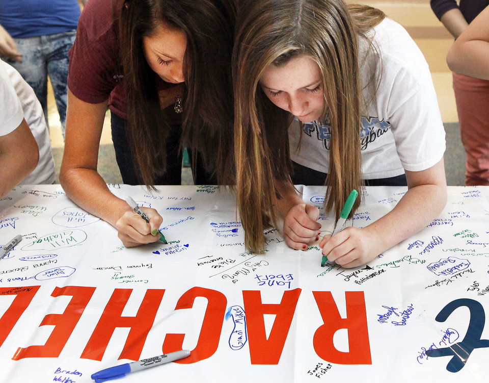 Photo - Students sign a banner indicating their willingness to accept Rachel's Pledge. The Edmond School District and the Edmond Public Schools Foundation are partnering to bring Rachel's Challenge to every middle school in the district as a result, in part, from a grant from a foundation donor. Students at Cheyenne Middle School watched a video presentation explaining the challenge and then were invited to sign their name to a banner, signaling their intent to accept Rachel's Pledge on Tuesday,  Aug. 28, 2012.  Rachel's Challenge is based on the life and writings of Rachel Scott, who was the first person killed during the Columbine High School massacre in 1999.  Her challenge is for individuals to make a permanent and positive change in their schools and community by starting a chain reaction of kindness and compassion.   Photo by Jim Beckel