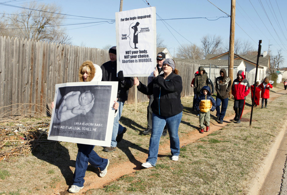 Angela Jeffers of Moore and Stephanie Tarlton of Oklahoma City carry signs as they walk down Western Avenue Monday while participating in the 2013 March for Life OKC from Our Lady's Cathedral, 3214 N Lake Ave., to the state Capitol building. <strong>PAUL B. SOUTHERLAND - PAUL B. SOUTHERLAND</strong>